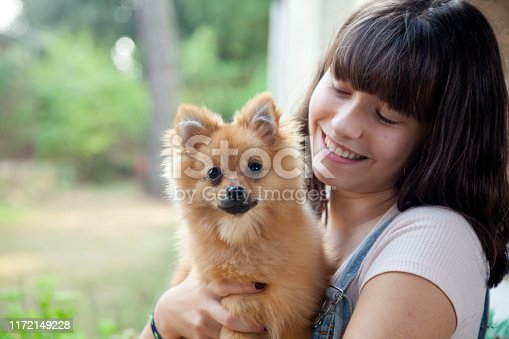 istock Happy girl with her little pomeranian 1172149228