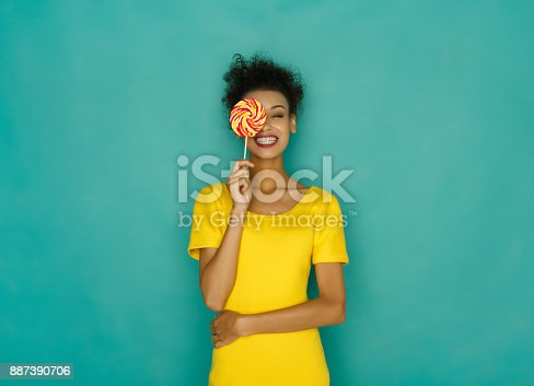 Smiling curly girl in bright yellow dress holding candy lollipop. Young cheerful woman hiding out eye with lollipop at azur studio background, copy space. Sweet life and confectionary