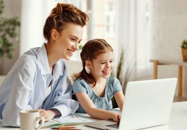 Glückliches Mädchen mit Mutter studieren online zu Hause – Foto
