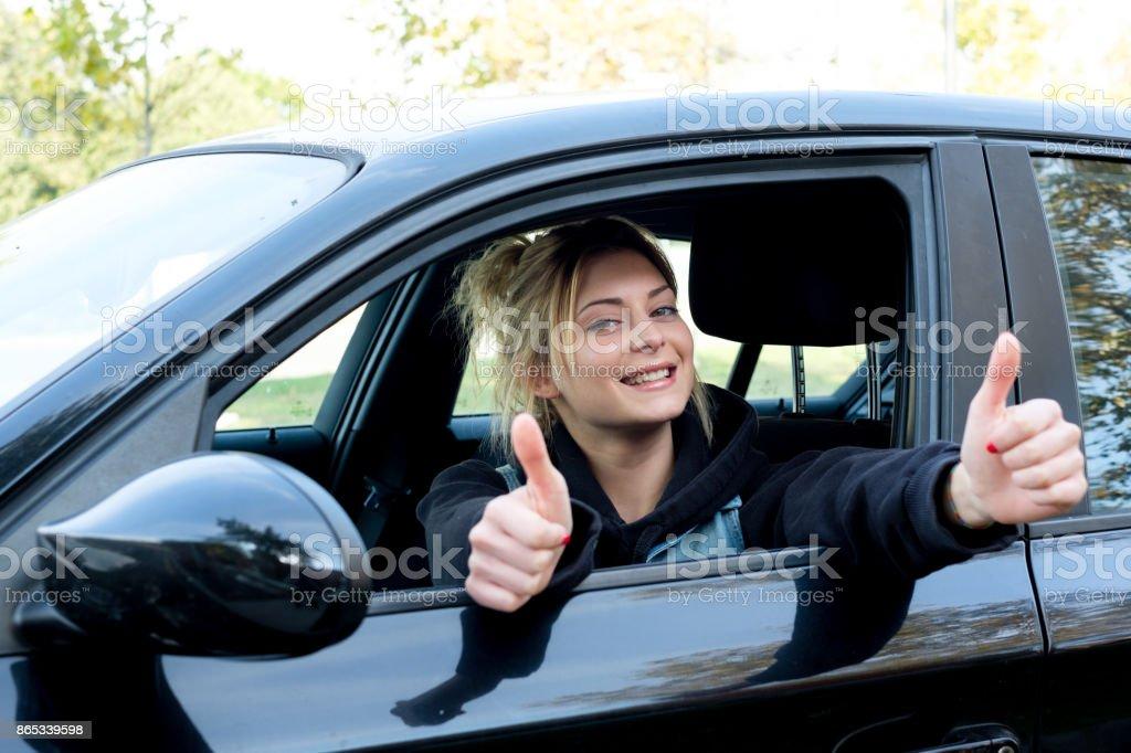 Glückliches Mädchen mit Daumen auf ihr neues Auto fahren – Foto