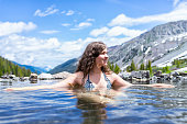 Happy girl woman swimming in hot springs water on Conundrum Creek Trail in Aspen, Colorado in 2019 summer in bathing suit with valley view