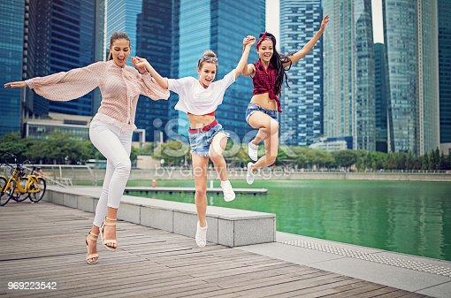 Happy girlfriends are running and jumping together