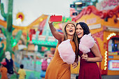 Happy girlfriends are taking selfie/making video call and make fun together in fun fair