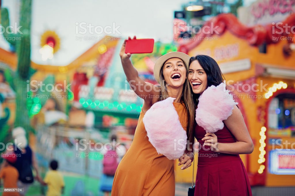 Happy girlfriends are taking selfie/making video call and make fun together in fun fair stock photo