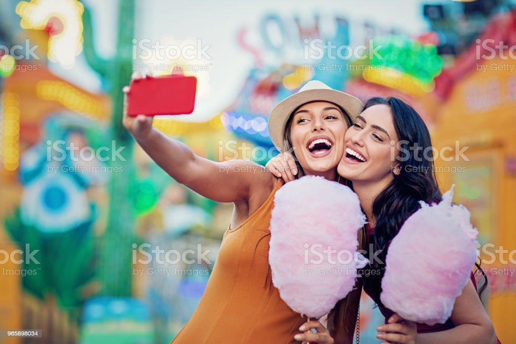 Gelukkig vriendinnen nemen selfie/maken video-oproep en maak plezier samen in een kermis - Royalty-free Arcade Stockfoto