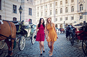 Happy girlfriends are walking in the city and make fun together