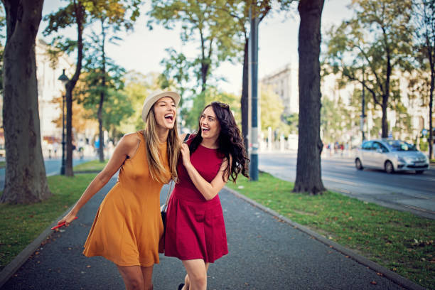 Happy girlfriends are walking in the city and make fun together stock photo