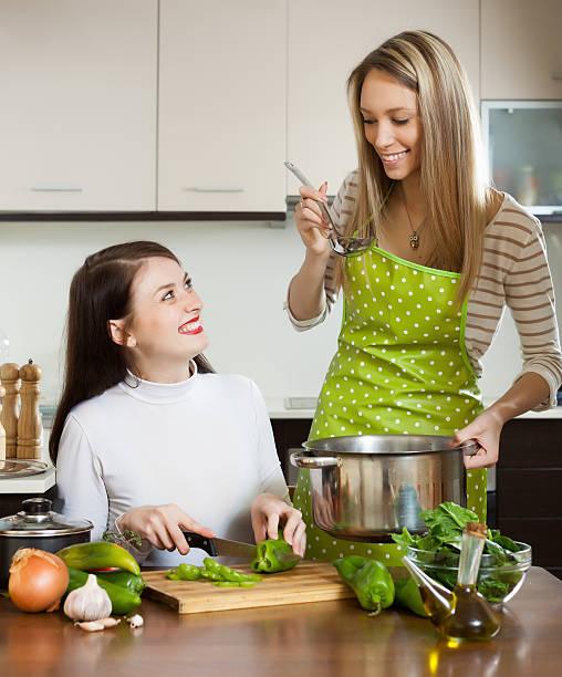 glückliche freundinnen kochen zusammen - pfannen test stock-fotos und bilder