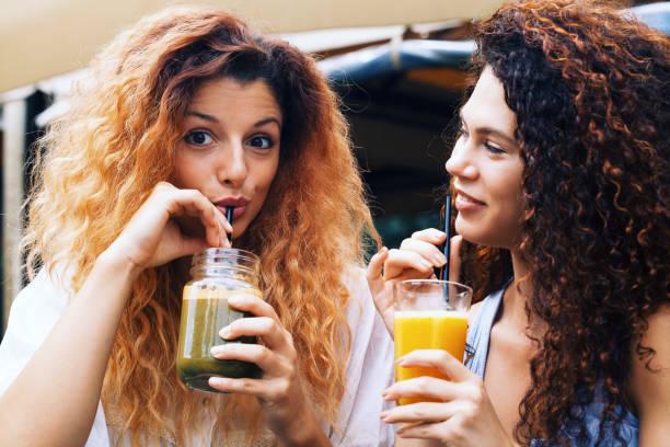 Happy girlfriends drinking juice stock photo