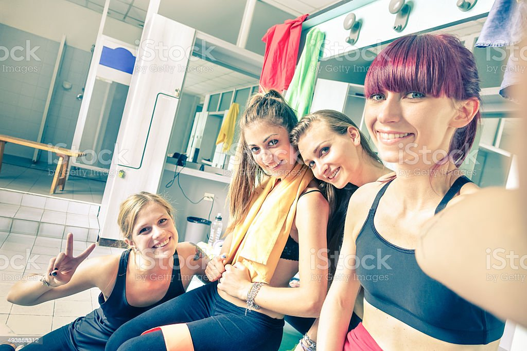 Happy girlfriends group taking selfie in gym dressing room Happy girlfriends group taking selfie in gym dressing room - Sporty female friends ready for fitness time - Healthy lifestyle and sport concept in training center - Bright vintage desaturated filter 2015 Stock Photo
