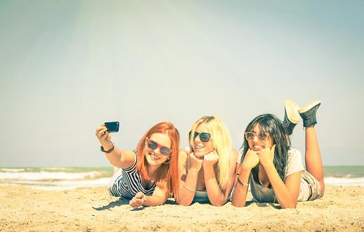 Happy girlfriends having fun and taking selfie at beach