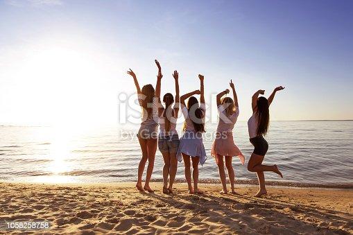 Happy girlfriends are having fun against sunset lake beach