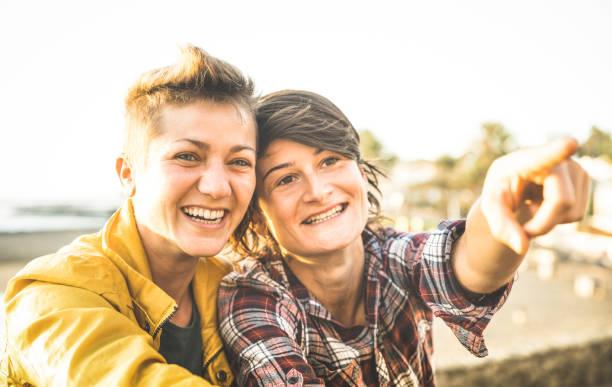 Copines heureuse en amour partage de temps ensemble au voyagent voyage pointant sur horizon - notion d'amitié femmes avec couple de filles s'amusant sur les vêtements de mode en plein air - lumineux coucher de soleil filtre chaud - Photo