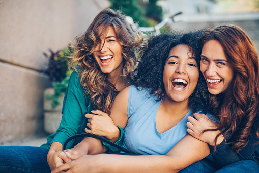 Three young women laughing outdoors