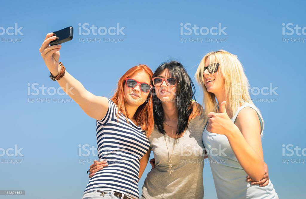 Happy girlfriends taking selfie against blue sky stock photo