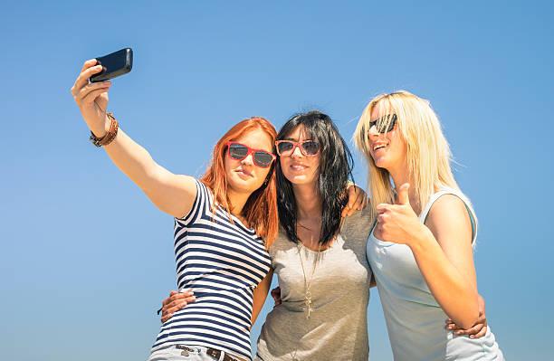 glückliche freundinnen schülern vor blauem himmel - hipster unterwäsche stock-fotos und bilder