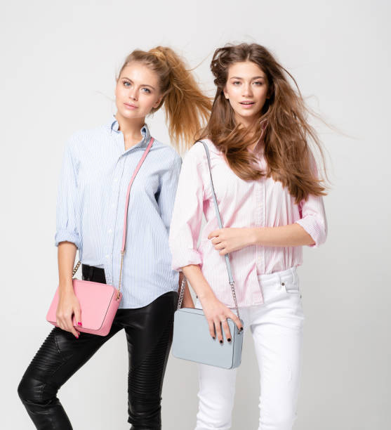 happy girlfriends women in shirts with stylish handbags. fashion spring image of two sisters. pastel pink and blue colors clothes. models with blonde and light brown hair. - spring fashion stock pictures, royalty-free photos & images