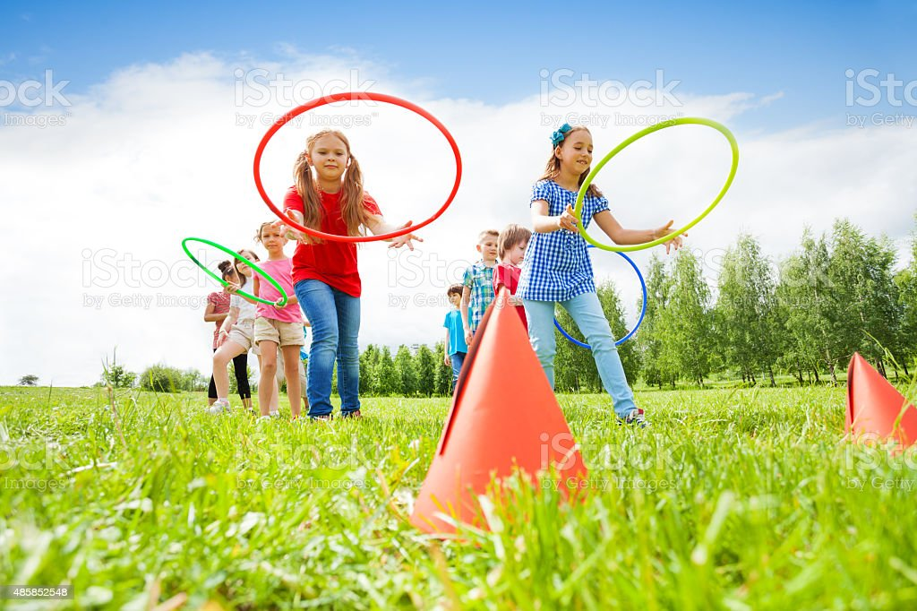 Happy girls and boys throwing colorful hoops stock photo