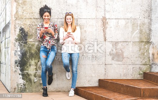 istock Happy girls best friends having fun outdoors with mobile smart phone - Friendship concept with millenial girlfriends on smartphones - Modern female lifestyle with women fashion blogger influencers 1129117753