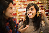 Image of two late teen happy, Asian girls of different ethnicity selecting and buying earrings at jewelry shop just before new year and Diwali festival in India. Two people, waist up, horizontal composition and selective focus with copy space.