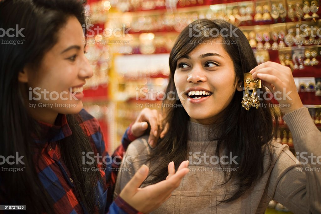 Happy girls buying earrings in jewelry shop before festival. stock photo
