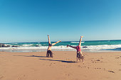 Happy girls doing gymnastics at the beach