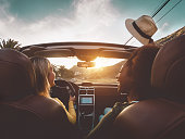 istock Happy girls doing road trip in tropical city - Travel people having fun driving in trendy convertible car discovering new places - Friendship and youth girlfriends vacation lifestyle concept 1254074198