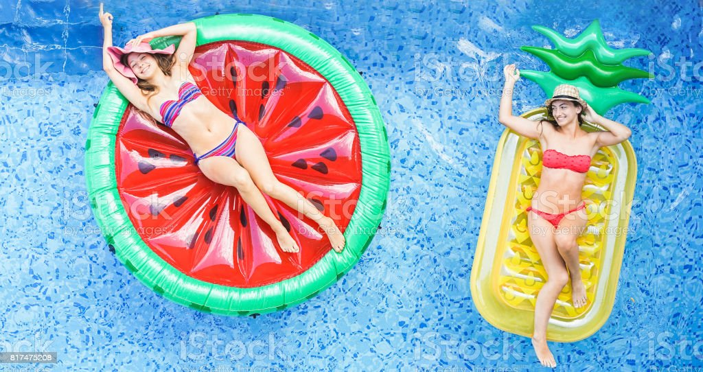 Happy girls floating with tropical fruit lilos inside swimming pool - Young women friends relaxing in summer vacation at resort hotel - Travel, chilling, holidays, youth concept - Warm filter stock photo