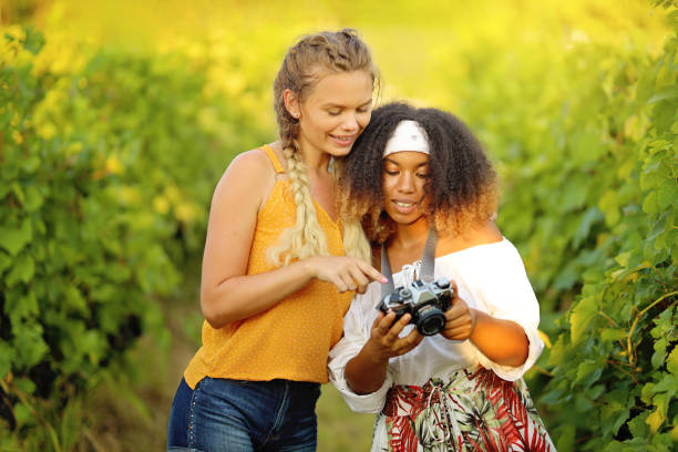 Happy girls friends taking some pictures outdoors stock photo
