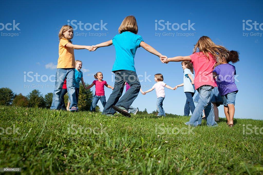 Heureuse filles tenant les mains dans un cercle extérieur, l'amitié, l'unité - Photo