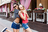 istock Happy girls hugging while walking in the city 931684710