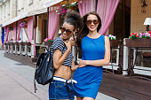 istock Happy girls hugging while walking in the city 931686514