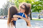 istock Happy girls hugging while walking in the city 932303284