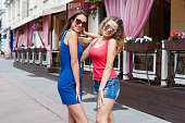 istock Happy girls hugging while walking in the city 932303916