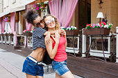 istock Happy girls hugging while walking in the city 936400610