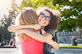 istock Happy girls hugging while walking in the city 938536522