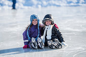 Two girls are outdoors on a cold winter day. They are dressed in warm clothing. They are taking a break from skating. They are sitting together on a frozen pond and embracing while smiling at the camera.