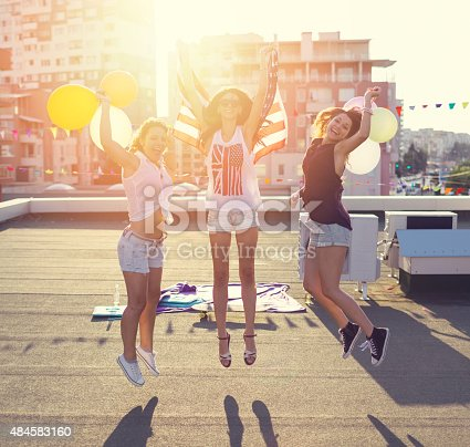 istock Happy girls jumping from joy on the rooftop 484583160
