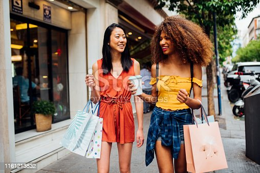 Women waking together after shopping and smiling