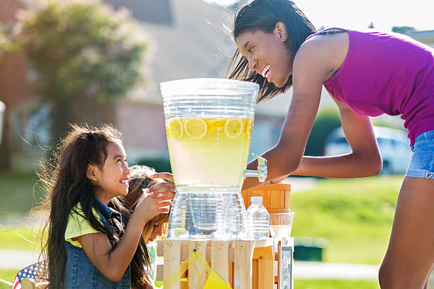 Happy girls sell lemonade to adult customer Little girls smile while serving lemonade to African American customer. The customer smiles at the girls while they serve her. lemonade stand stock pictures, royalty-free photos & images