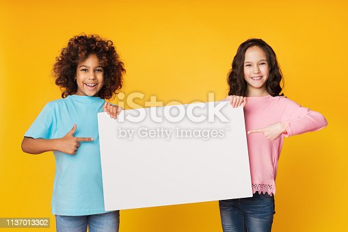 istock Happy girls showing blank board and pointing on it 1137013302