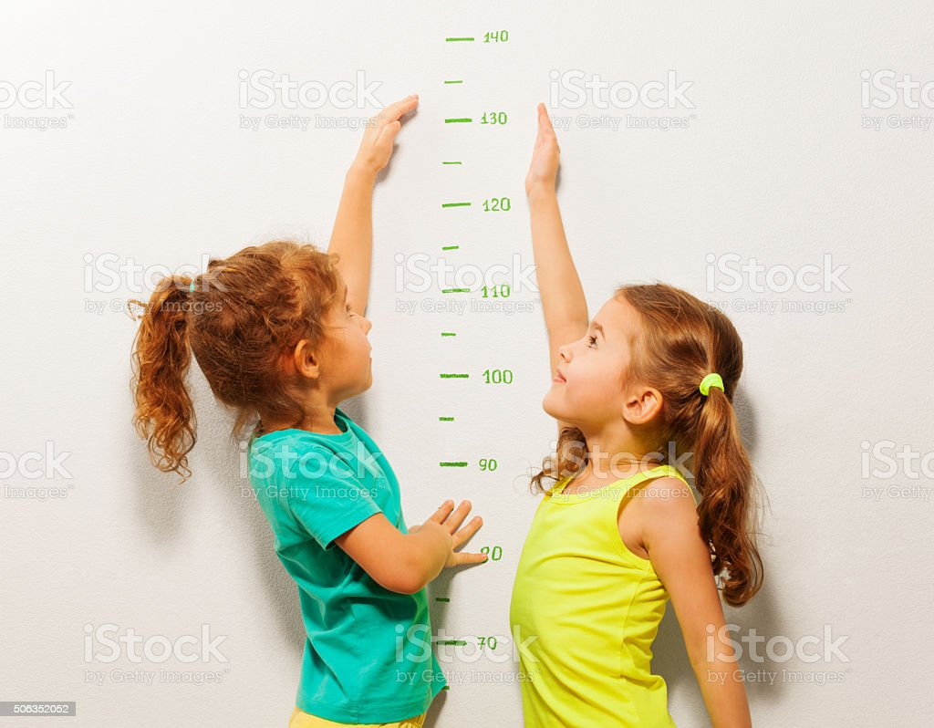 Happy girls stretch hands up on wall scale stock photo