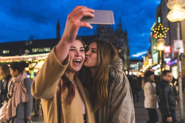 glückliche mädchen, die eine selfie zusammen zu weihnachten markt münchen - weihnachtsfeier münchen stock-fotos und bilder