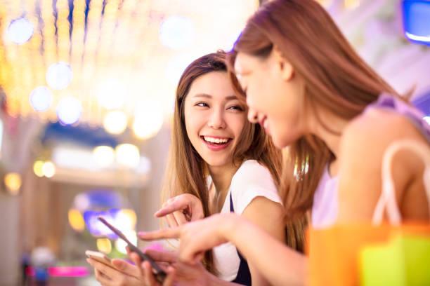 happy girls watching phone in the shopping mall - online shopping imagens e fotografias de stock