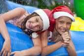 two little girls in inflatable pool wearing christmas hats
