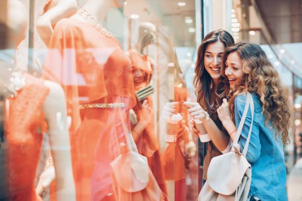 Happy girls window shopping stock photo