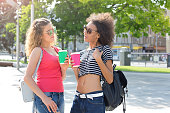 istock Happy girls with take away coffee outdoors 931679424
