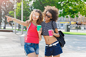 istock Happy girls with take away coffee outdoors 932303430