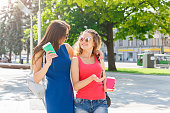 istock Happy girls with take away coffee outdoors 932303620