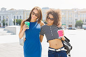 istock Happy girls with take away coffee outdoors 936400260